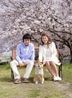 ベンチに座るカップルと犬