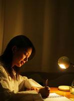 暗い部屋で文字を書いている日本人女性