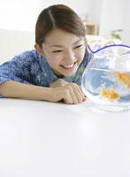 金魚を眺める和服の女性