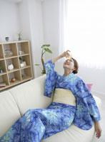 グラスを額に当てる和服の女性