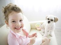 キャンディーを持つ女の子と見つめる犬