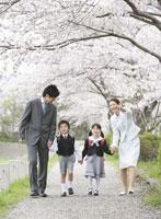 土手を歩く四人の家族