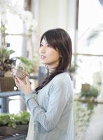 花屋でサボテンを手に持つ女性
