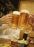 乾杯でぶつかりあうビールグラス