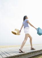 海辺を歩くショートパンツ姿の女性
