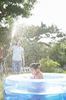 プールの中でホースの水しぶきを浴びる女の子