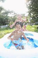 水しぶきを上げて庭のプールで遊ぶ三人の姉弟 11004028614| 写真素材・ストックフォト・画像・イラスト素材|アマナイメージズ