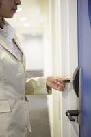 鍵がかかった会社のドアを開けるビジネスウーマン
