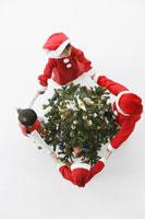 サンタ姿でツリーの周りを回る子供たち