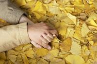 落ち葉の上で固く繋がれた男女の手