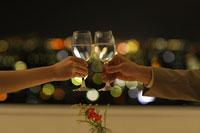 夜景をバックに乾杯する男女の手