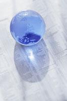 英字新聞の上のガラスの地球儀