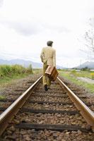 線路を歩く男性の後ろ姿