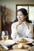 料理を前に微笑む女性 11004030731  写真素材・ストックフォト・画像・イラスト素材 アマナイメージズ