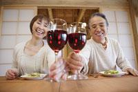 ワイングラスを合わせて差し出す笑顔の男女
