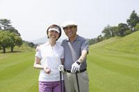 ゴルフをする中高年カップル