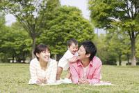芝生に寝ころぶ日本人家族 11004032831| 写真素材・ストックフォト・画像・イラスト素材|アマナイメージズ