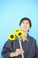 ヒマワリの花を持った浴衣姿の男性