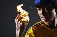 燃えるボールをにぎる男性
