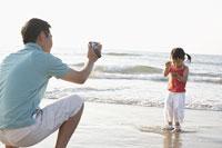 海辺でビデオを撮る親子
