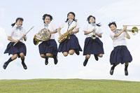 楽器を持ってジャンプする女子中学生