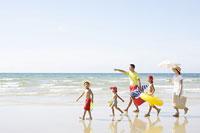 波打ち際を歩く家族
