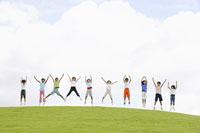 草原でジャンプをする子供達