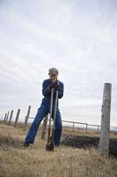 作業服を着て牧場で働く男性