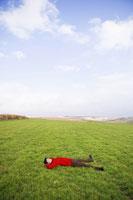 草原で仰向けに寝転ぶ男性