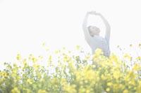 菜の花畑で背伸びする女性
