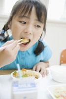 給食を食べる小学生の女の子