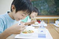 給食を食べる日本人の小学生