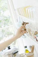 香辛料の瓶を取る手とキッチンイメージ
