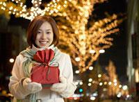 イルミネーションとプレゼントを持つ女性