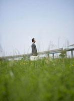 草原にたたずむスーツ姿のビジネスマン