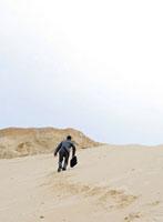 砂浜を登るビジネスマン