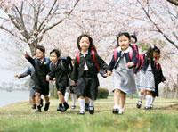 桜の花と走る新入生の子供達