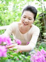 庭の植物の世話をするシニア女性
