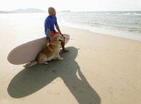 サーフボードに座る日本人男性と犬