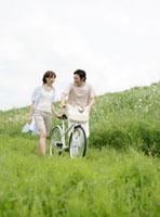 自転車をおして歩くカップル