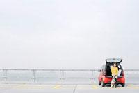 車のトランクに腰掛る女性とダルメシアン