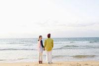 浜辺に佇み海を眺める男女の後ろ姿