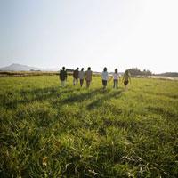 草原を歩く若者の後ろ姿