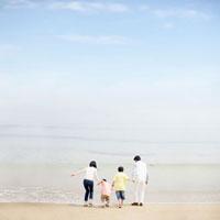 波打ち際に立つ家族