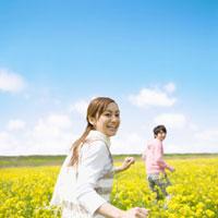 菜の花畑を走るカップル