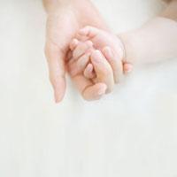 赤ちゃんの手を包む母親の手