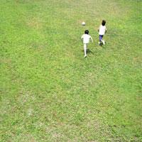 草原でサッカーをする男の子