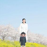 桜並木に立つ親子