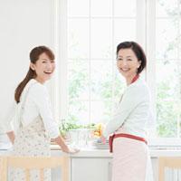 キッチンに立って料理をする親子