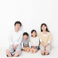 壁にもたれて座る家族